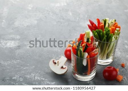 Sliced vegetables in glasses on wooden table