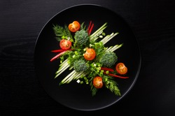 Sliced vegetables lie on a black plate on a black background photographed. Vegetables are photographed horizontally.