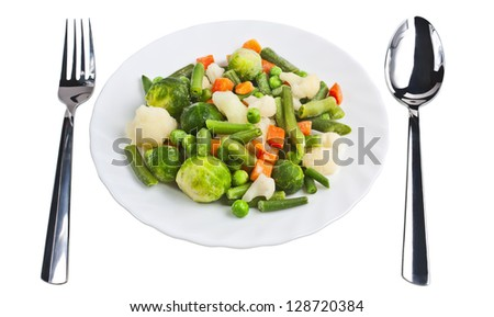Sliced vegetables on a plate with fork and spoon on the table isolated easy diet food