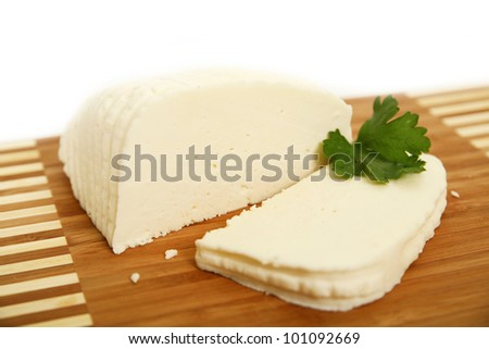 sliced white goat cheese on wooden plate