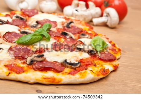 sliced whole salami and mushrooms pizza with ingredients  on a wooden table