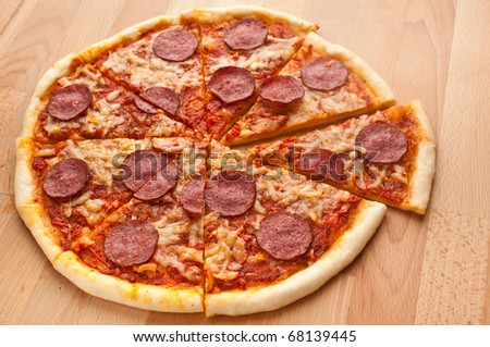 sliced whole salami pizza on a wooden table