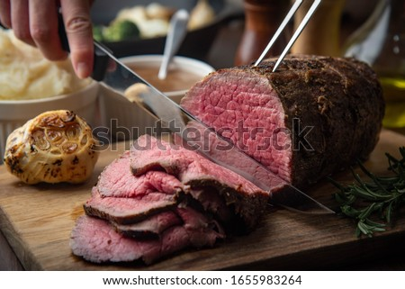 sliceing roasted eye of round beef with knife Stockfoto ©
