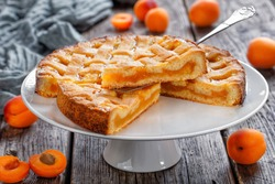 slices of apricot shortcrust pie with a lattice pie crust topping on a cake stand with vintage cake shovel on a rustic wooden table with fresh apricot and grey cloth at the background, landscape view