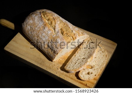 slices of artisan spelled bread on black background