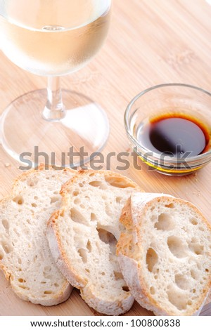 Slices of baguette with olive oil and balsamic vinegar, with a glass of wine - stock photo