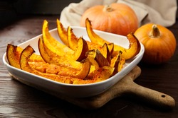 Slices of baked pumpkin in white ceramic bowl on brown wooden table, closeup, selective focus. Vegetable dish, vegan diet, healthy food