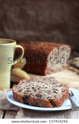 slices of banana bread with nuts in the white plate with a loaf of bread in the background