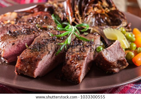 Slices of beef steak served with baked artichoke on a plate