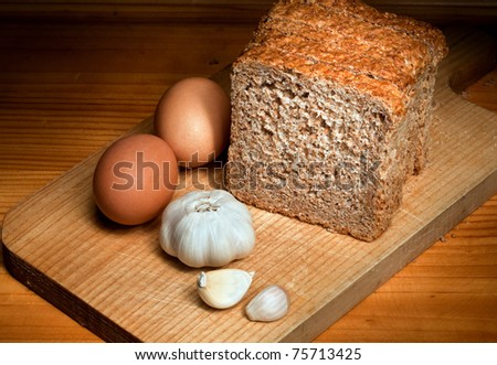 slices of bread, garlic and eggs on a wooden table