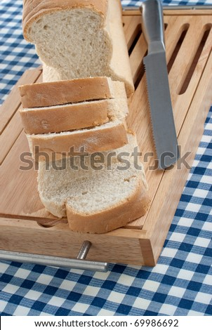 Slices of bread on top of wooden board and a blue square pattern towel.