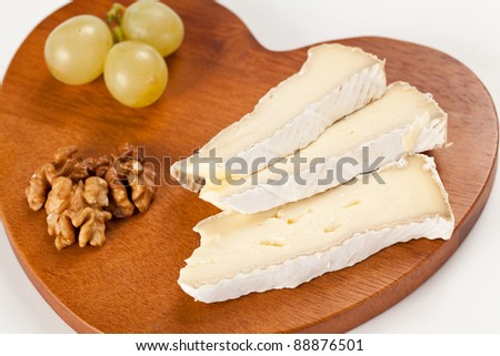 Slices of Brie french cheese with grapes and nuts over an hearth shaped wooden board in isolated studio shot