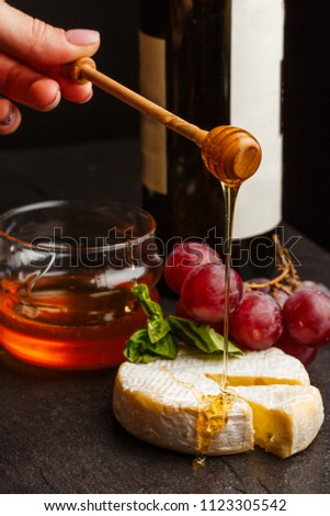 Slices of camembert or brie cheese pour honey  on dark background. piece of tasty France cheese with grapes, honey, wine, nuts. top view