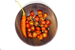 slices of cayenne pepper (capsicum annuum) on a round wooden plate isolated on white background
