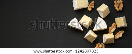 Slices of cheese camembert or brie  with walnuts, top view. Milk production. Overhead view. Flat lay. From above. Space for text.