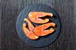 Slices of cold-smoked arctic char on a round slate on a dark wooden background, top view, close-up