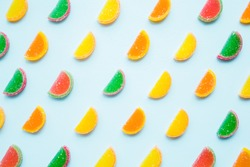 Slices of colorful candied fruit jelly on light pastel blue background. Sweets pattern. Top view.