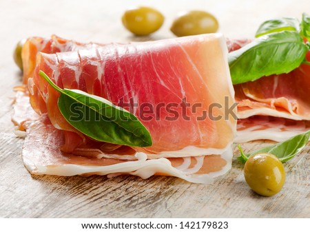 Slices of cured ham on a wooden table . Selective focus