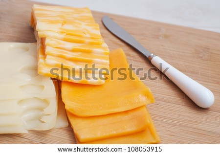 Slices of different kinds of cheese - swiss, cheddar, marble