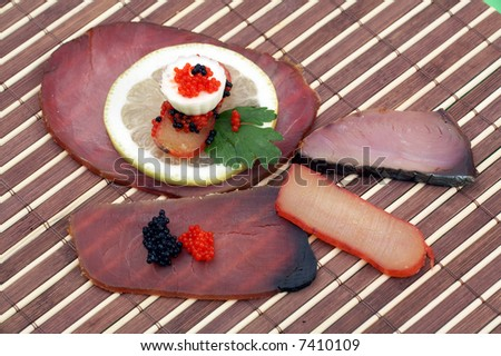 slices of dried fish, caviar, lemon and cheese