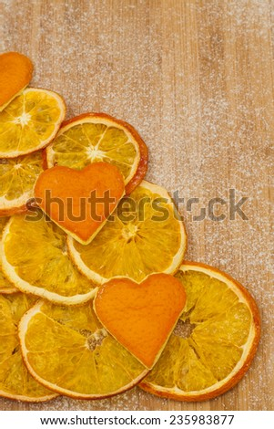 slices of dried orange peel and hearts of on a wooden background