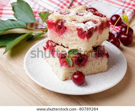 Slices of fresh cherry iced sponge cake with berries