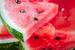 slices of fresh juicy organic watermelon on a wooden background