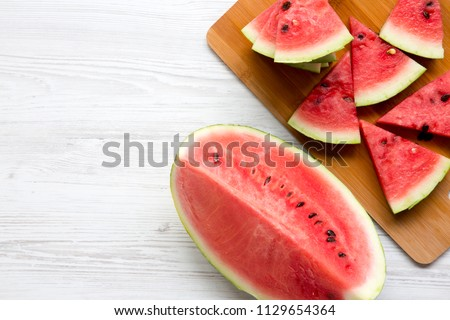 Slices of fresh watermelon on bamboo board, from above. Top view. Copy space.