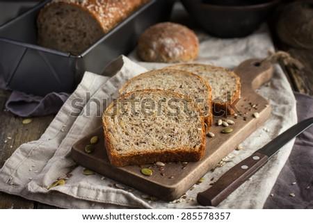 slices of freshly baked  multigrain bread on rustic background