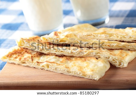 Slices of gozleme with cheese on a cutting board