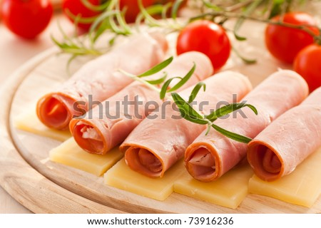 Slices of ham and cheese with rosemary