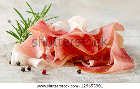 slices of ham and herbs on a wooden table . Selective focus.