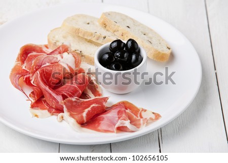 Slices of ham, Black olives and ciabatta on white plate