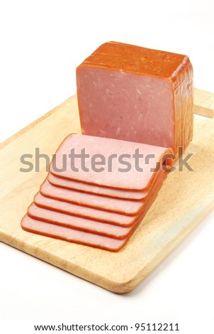 Slices of ham on a wooden board.