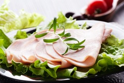 Slices of ham on lettuce with rosemary.