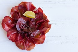 Slices of Italian meat Bresaola served with olive oil and lemon on a plate on white background with place for text. Traditional appetizers antipasti. Top view. Copy space.