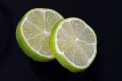 Slices of juicy green lime on a black surface