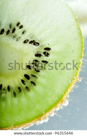 Slices of kiwi closeup backlit with seeds in water