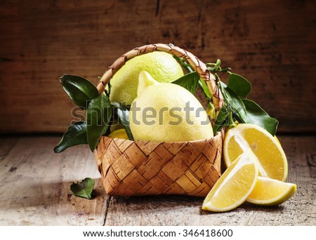 Slices of lemon and cut lemons with leaves in a wicker basket on an old wooden table in rustic style, selective focus #346418600