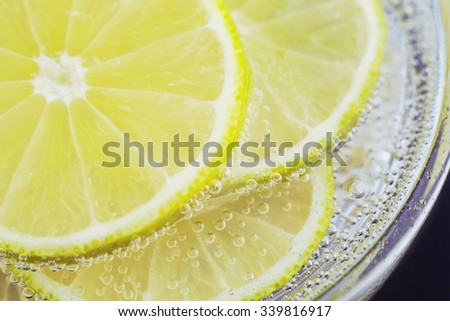 Slices of lemon? in soda water. Lime Cocktail. The liquid drink. Bubbles of carbon dioxide. The background texture. Tropical citrus fruit. Macro lemon?. Ingredient.