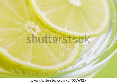 Slices of lime in soda water. Lime Cocktail. The liquid drink. Bubbles of carbon dioxide. The background texture. Tropical citrus fruit. Macro Lime. Ingredient.