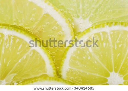 Slices of lime in soda water. Lime Cocktail. The liquid drink. Bubbles of carbon dioxide. The background texture. Tropical citrus fruit. Macro Lime, macro lemon. Ingredient.