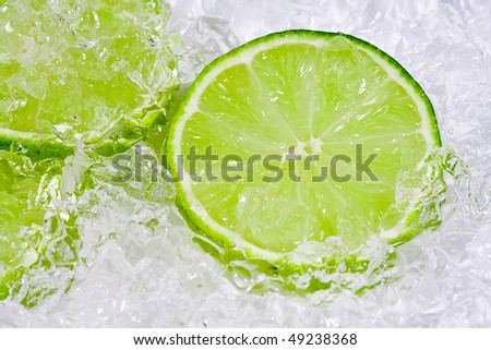 Slices of lime with crushed ice on white background