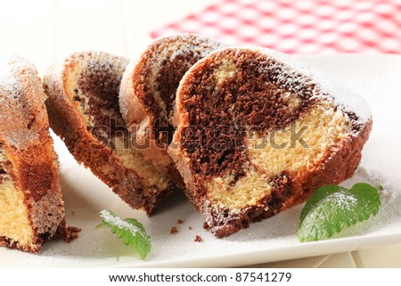 Slices of marble cake sprinkled with icing sugar
