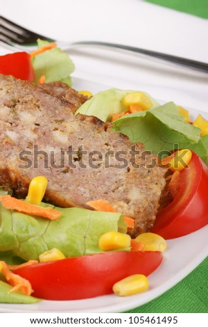 Slices of meatloaf served on a white plate with fresh mixed salad
