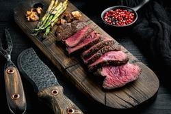 Slices of Medium rare grilled marbled meat beef steak set, tenderloin or fillet mignon cut, on wooden serving board, on black wooden table background