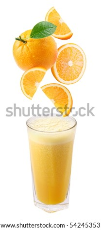 Slices of orange fall into a glass of fresh juice