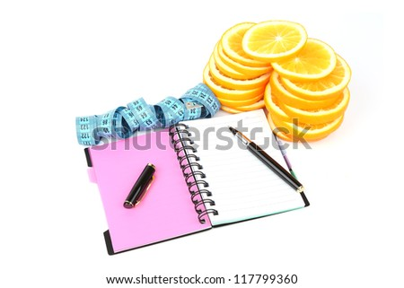 slices of orange, notebook, pen, and meter isolated with soft shadow and reflection over white background