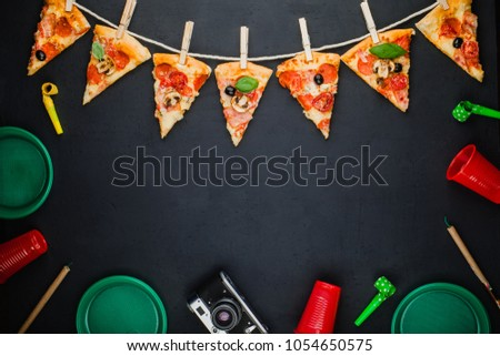 Slices of pizza in the form of a garland with the attributes of a party. Pizza slices on a gray concrete background. Space for text. Pizza menu. Birthday with fast food.