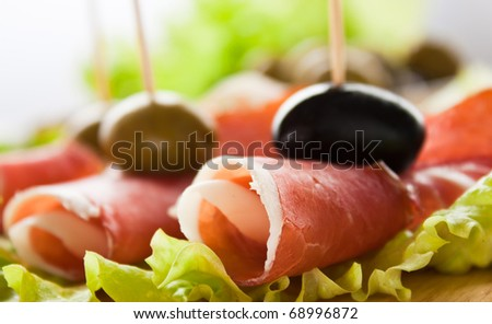 Slices of prosciutto rolled up and arranged on a lettuce leaf. Shallow depth of field.